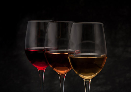 Red, pink and white wine in glasses on black grunge background