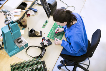 High angle view of female technician soldering circuit board at desk in factory