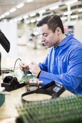 Mature male technician soldering circuit board at desk in industry