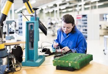 Mid adult female electrician working on circuit board at desk in industry