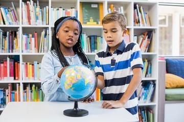 School kids looking at globe in library