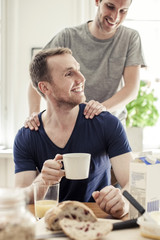 Young gay man massaging partner having breakfast at table