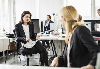 Mid adult businesswoman gesturing while looking at colleague in office