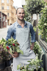 Portrait of male florist holding potted plant while standing outside flower shop