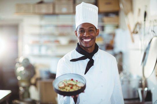 Portrait of head chef presenting salad