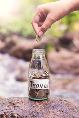 Saving coins in the glass jar for travel purpose.