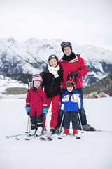 Portrait of family in ski-wear standing together against mountain range