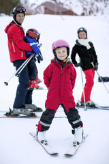 Portrait of girl in ski-wear smiling with family standing in background