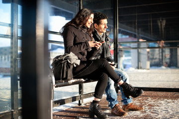 Happy friends in warm clothes holding mobile phones while looking away