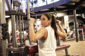 Frau macht Rückenübung mit dem Kabel