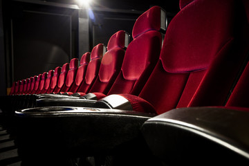 Row of red velvet seats in theater