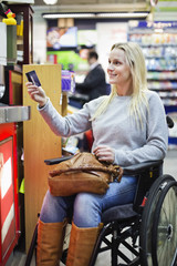 Disabled woman in wheelchair paying through credit card at supermarket