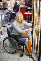 Happy disabled woman in wheelchair at refrigerated section of supermarket looking away