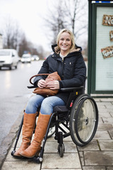 Portrait of happy disabled woman in wheelchair smiling outdoors