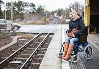 Disabled woman in wheelchair waiting for the train at railway station