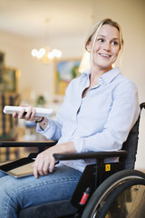 Happy disabled woman in wheelchair with digital tablet looking away while using remote control