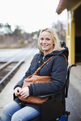 Portrait of happy disabled woman in wheelchair at railway station platform