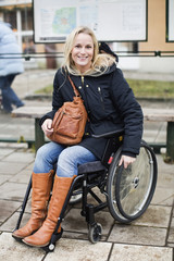 Portrait of happy disabled woman in wheelchair at bus stop