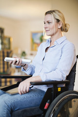Disabled woman in wheelchair with digital tablet using remote control
