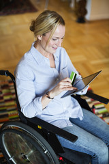 Disabled woman in wheelchair using digital tablet for online shopping