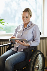 Disabled woman using digital tablet while sitting in wheelchair at home