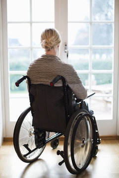 Rear view of disabled woman in wheelchair against french doors