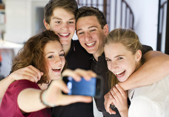 Happy young friends taking self portrait through cell phone