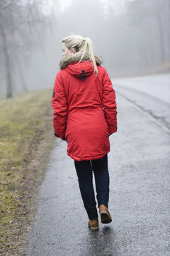 Rear view of young woman in winter coat walking on road