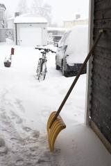 Car and bicycle parked with snow shovel in front