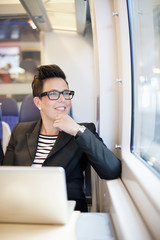 Thoughtful mid adult businesswoman with laptop looking out from train window