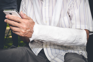 Save Download Preview Close Up and color filler of senior patient using mobile smart phone with broken arm