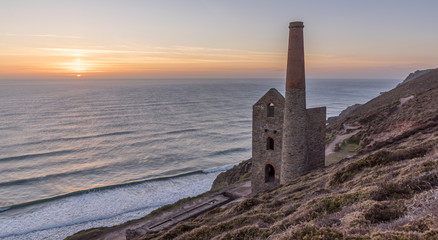 The ruin of a Cornish tin mine, on the edge of a cliff, with the sun setting into the ocean behind it
