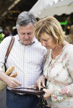 Couple using digital tablet with market in the background