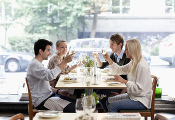 Group of friends toasting wineglasses at restaurant table