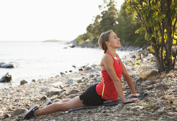 Young woman practicing yoga at riverbank