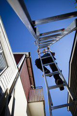 Low angle view of man climbing ladder against clear sky