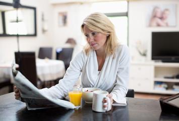 Mid adult woman in bathrobe reading newspaper while having breakfast