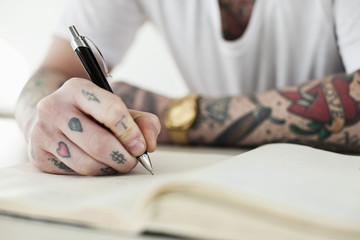 Midsection of a tattooed man writing