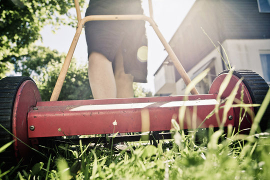Midsection of a woman mowing grass in lawn