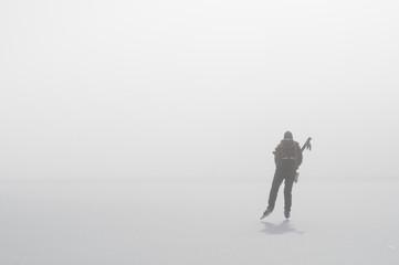 Man ice skating on frozen lake in fog