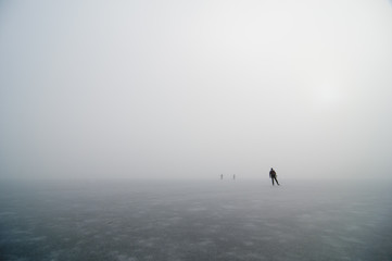 People hiking on ice rink in fog