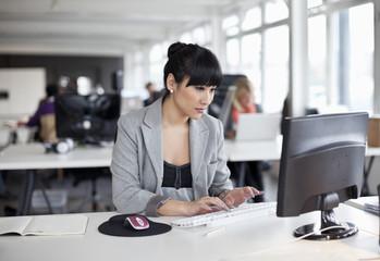 Businesswoman sitting at desk typing