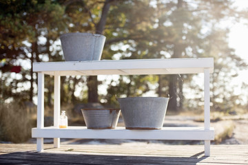 Metal buckets on shelf outdoors