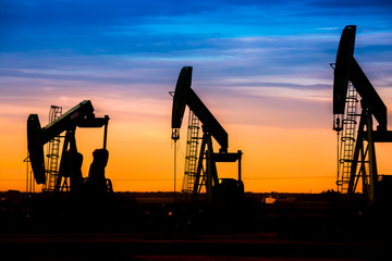 Silhouette of Oil pumps at oil field with sunset sky background