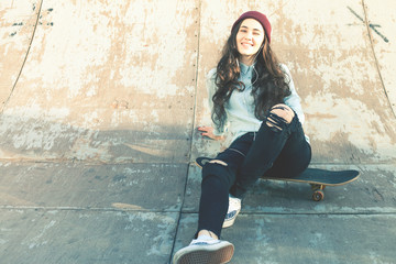 Hipster skateboarder girl with skateboard outdoor sitting at skatepark