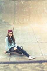 Hipster skateboarder girl with skateboard outdoor at skatepark