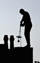 Chimney sweep working on roof at dusk