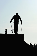 Silhouette of chimney sweep on roof