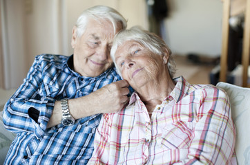Loving senior man with wife sitting on sofa in living room