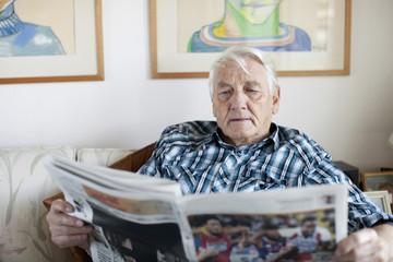 Senior adult man reading newspaper in living room